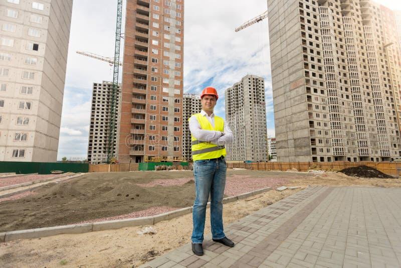 Man i hjälm och säkerhetsvästanseende på byggnadsplats arkivfoton