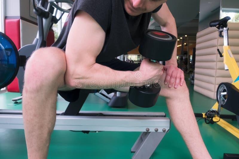 Man i idrottshall med hantelcloseupen arkivfoto