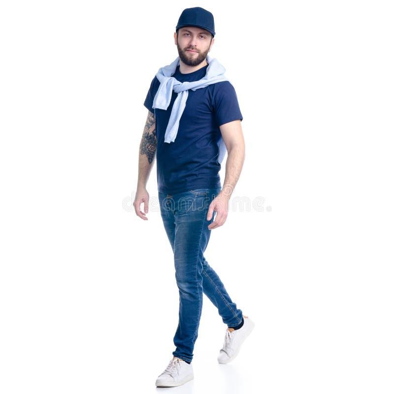 Man i jeans, t-skjorta och lock som går att le arkivfoton