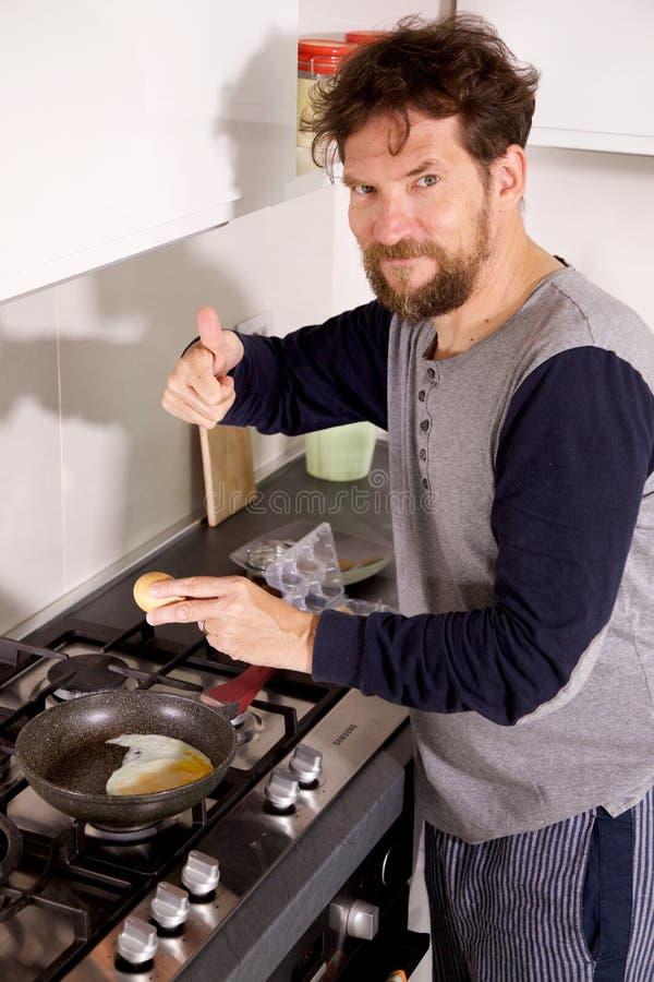 Man i kök i morgonen som lagar mat det ok tecknet för ägg arkivbilder