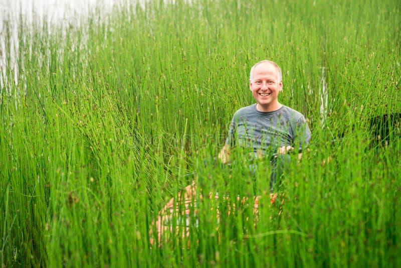 Man i kajak som paddlar till och med kust- gräs fotografering för bildbyråer