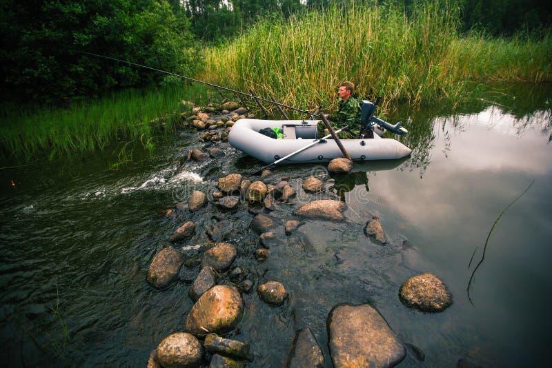 Man i kamouflagemetspö på floden på ett rubber fartyg Natur arkivfoton
