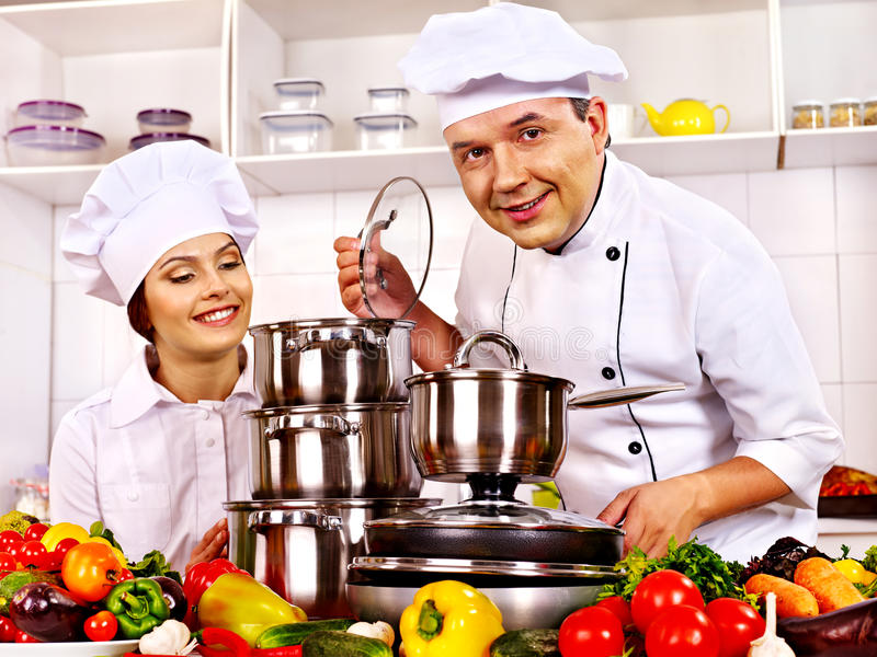 Man i kockhatt- och kvinnamatlagning. royaltyfri bild