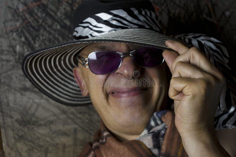 Man i kvinnlig bredbrättad hatt royaltyfria foton