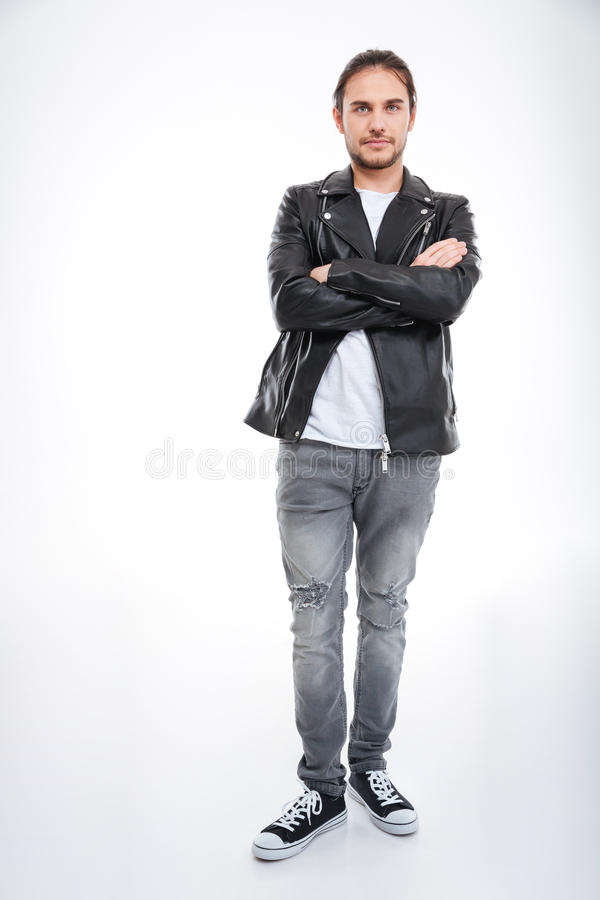 Man i läderomslaget och jeans som står med korsade armar royaltyfri foto