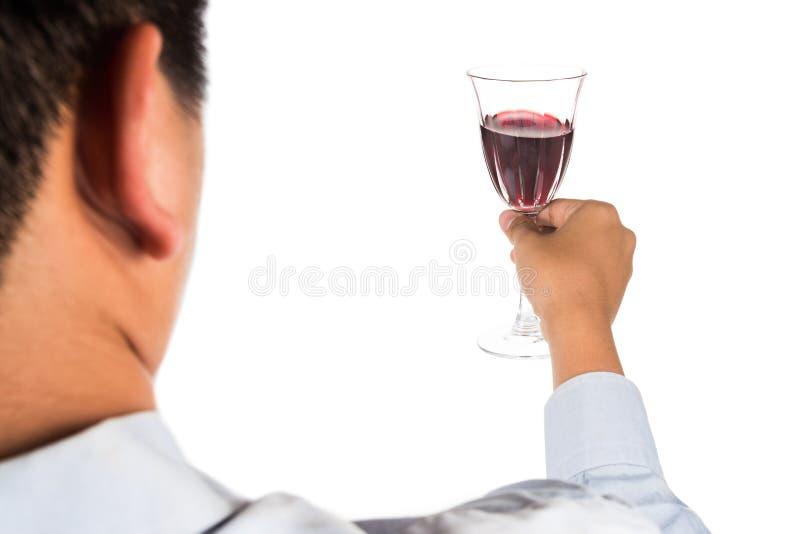 Man i lång muffskjorta som rostar rött vin i crystal exponeringsglas royaltyfri fotografi