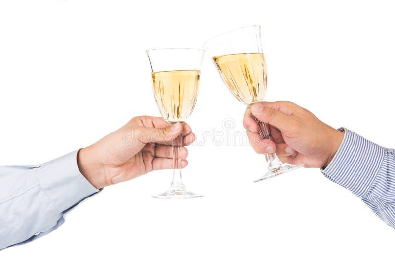 Man i lång muffskjorta som rostar vitt vin i crystal exponeringsglas royaltyfri bild
