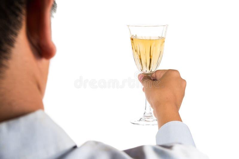 Man i lång muffskjorta som rostar vitt vin i crystal exponeringsglas royaltyfria bilder