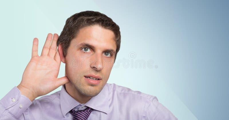 Man i lavendelskjorta med handen på örat mot blå bakgrund arkivbild