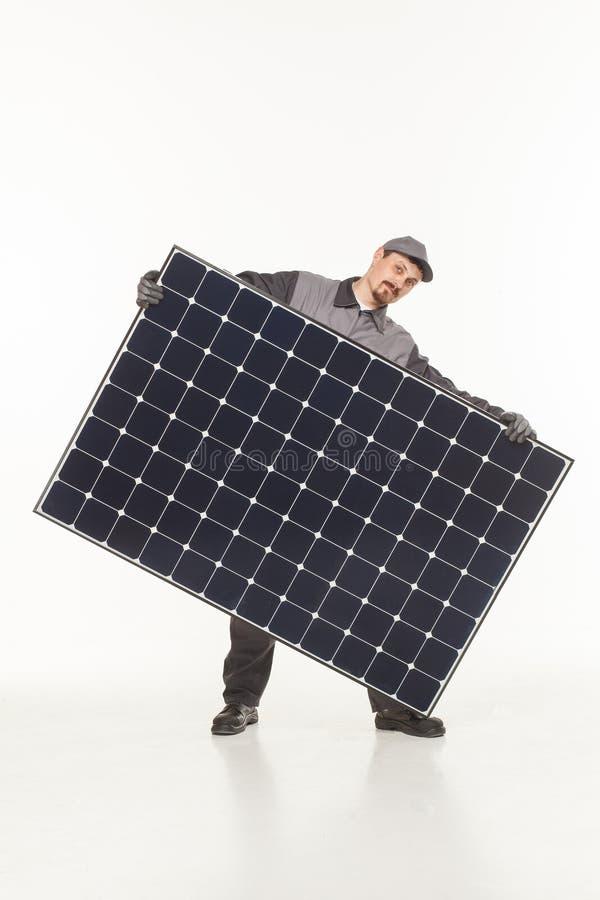 Man i likformig med ett sol- batteri arkivbilder