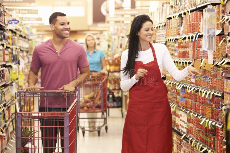 Man i livsmedelsbutikgång av supermarket med försäljningsassistenten arkivbilder