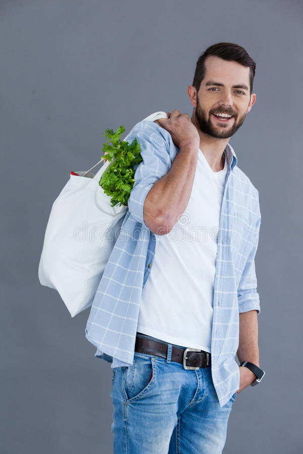 Man i ljus - blå skjorta som bär en livsmedelsbutikpåse royaltyfria foton