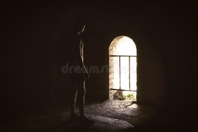 Man i mörkret som klargöras av solen i mystisk slott royaltyfri fotografi