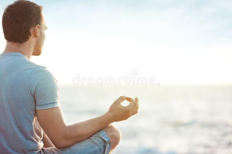 Man i meditation nära havet arkivbilder