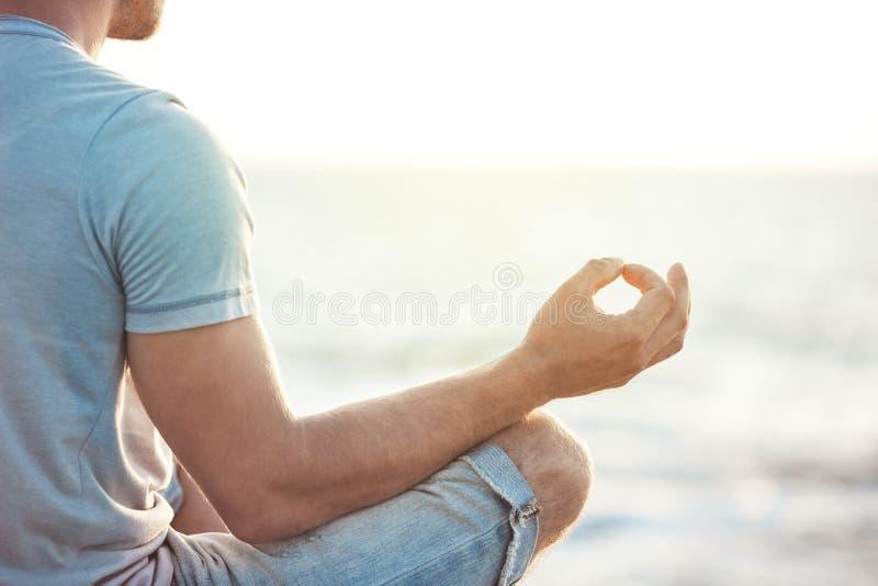 Man i meditation nära havet fotografering för bildbyråer