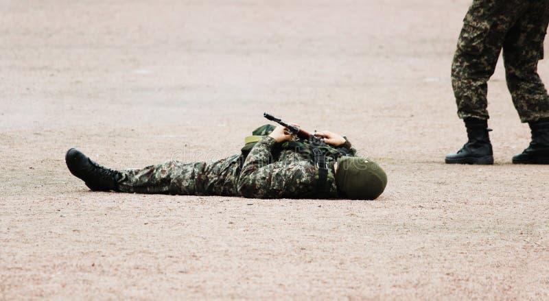 Man i militära kamouflagekläder och en maskering som ligger på hans baksida sanden med maskingevär i hand under demonstrationspen royaltyfria foton