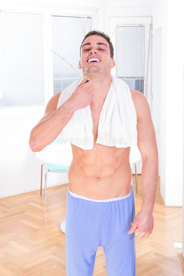 Man i pyjamas som rakar skägget med rakkniven i morgonen fotografering för bildbyråer