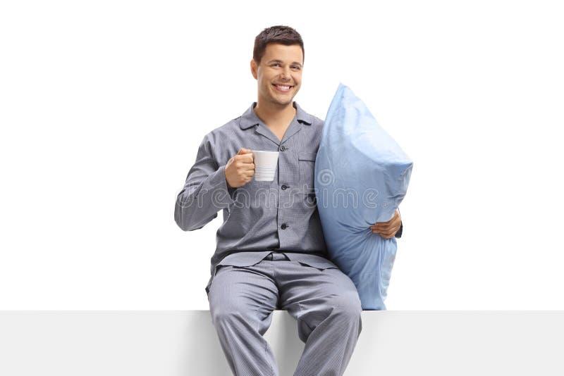 Man i pyjamas som rymmer en kopp och en kudde och sitter på en panel arkivfoton