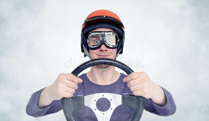 Man i röd hjälm och skyddsglasögon med styrninghjulet begrepp för bilchaufför fotografering för bildbyråer