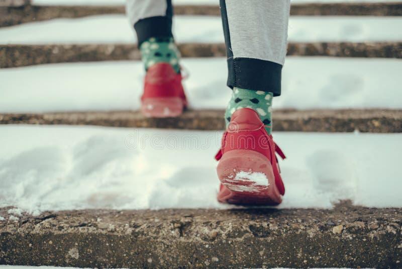 Man i röda gymnastikskor som går upp den snöig trappan arkivfoto