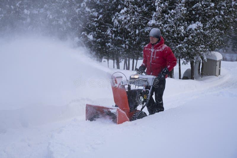 Man i rött lag genom att använda snöthroweren i körbana royaltyfri foto