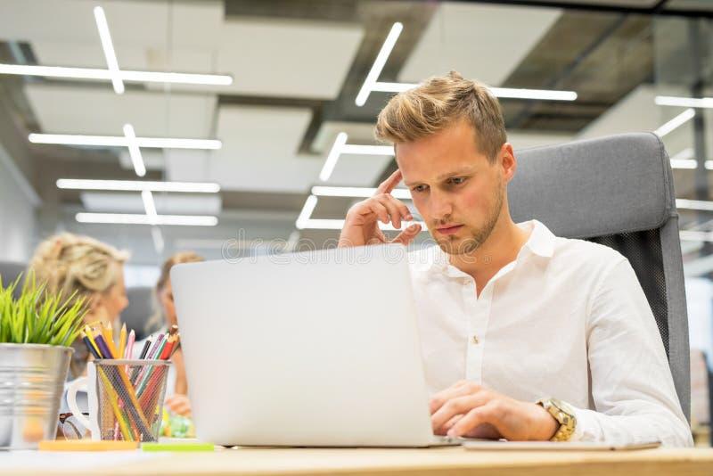 Man i regeringsställning som arbetar på bärbara datorn arkivfoton