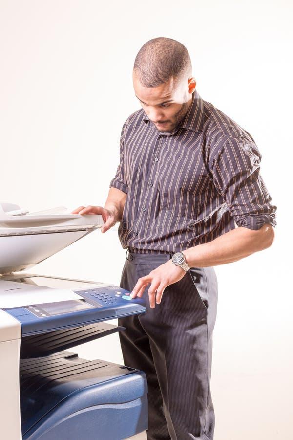 Man i regeringsställning som gör kopior genom att använda fotokopiatorn fotografering för bildbyråer