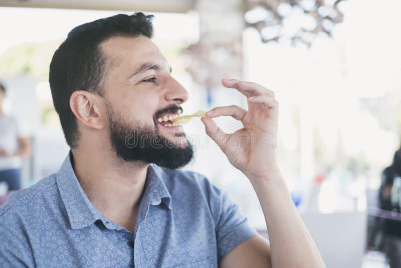 Man i restaurang som äter chiper royaltyfria foton