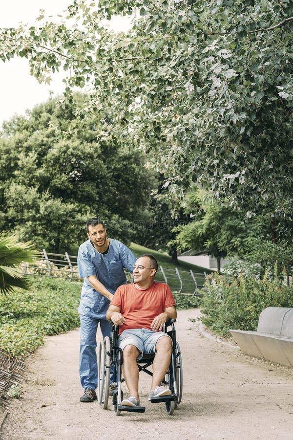 Man i rullstol som går med hans vaktmästare arkivfoto