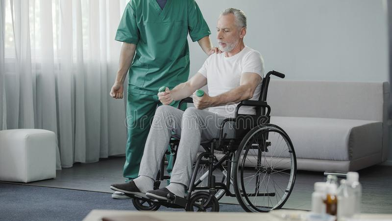 Man i rullstol som pumpar hans svaga muskler med hjälp av sjuksköterskan, rehabilitering royaltyfria foton