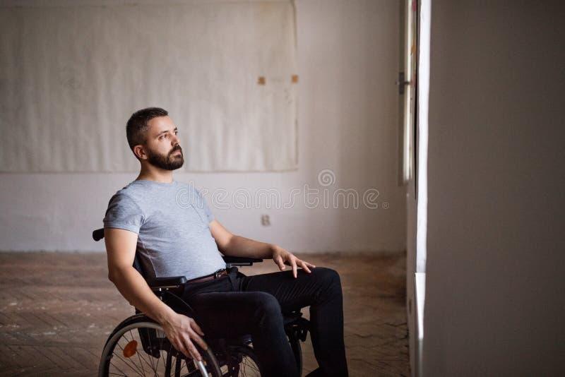 Man i rullstolen som ser ut ur fönstret royaltyfria foton
