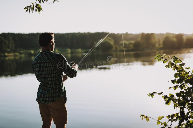 Man i rutigt skjortafiske på floden i sommar arkivbild
