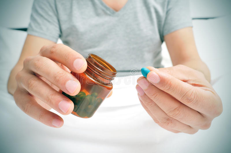 Man i säng omkring som tar en blå preventivpiller fotografering för bildbyråer