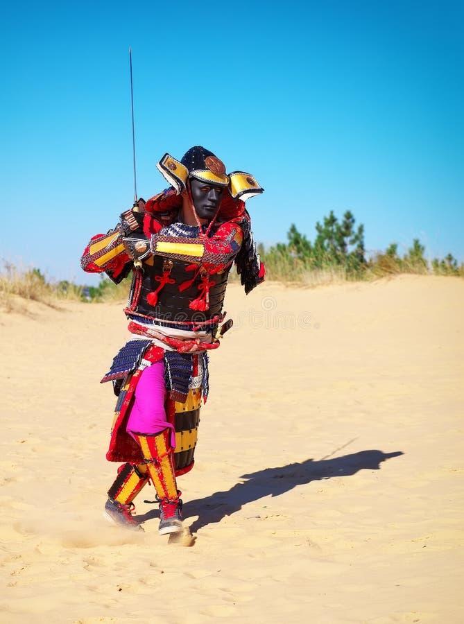 Man i samurajdräkt med svärdspring på sanden arkivbilder