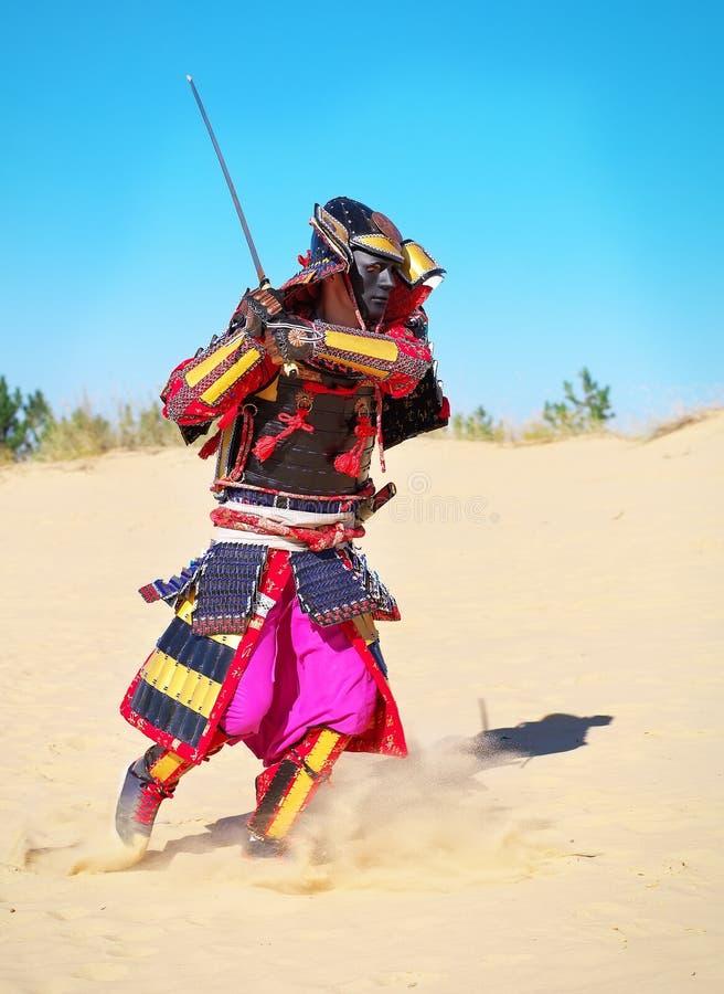 Man i samurajdräkt med svärdspring på sanden royaltyfri fotografi