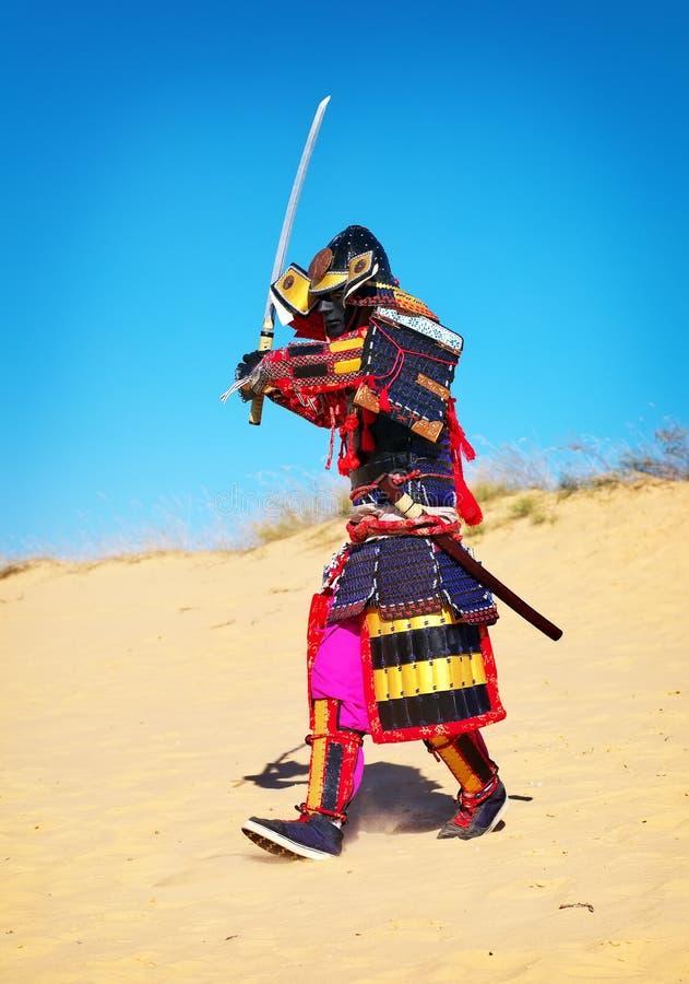 Man i samurajdräkt med svärdspring på sanden Män i sa royaltyfri fotografi