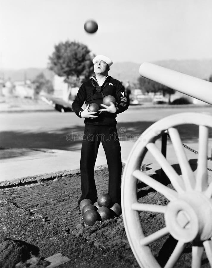 Man i sjömanlikformign som försöker att jonglera kanonbollar (alla visade personer inte är längre uppehälle, och inget gods finns royaltyfria foton
