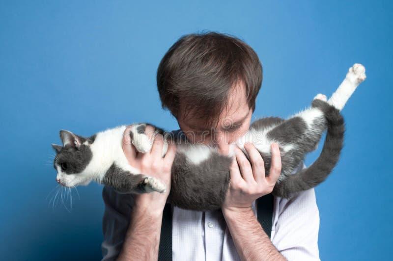 man i skjortan och den svarta suspenderen som rymmer och kysser gråa för mage den gulliga och vita katten royaltyfri fotografi