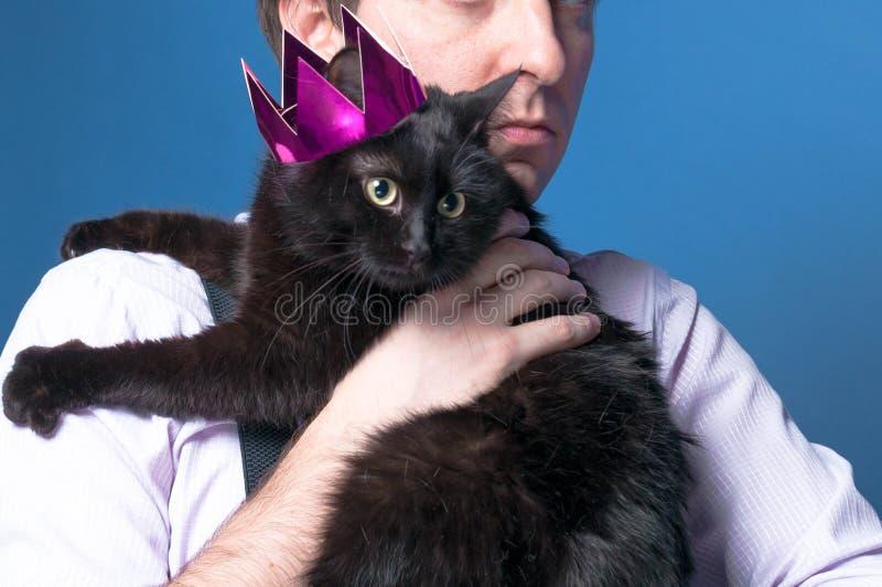 Man i skjortan som rymmer den svarta katten i rosa skinande krona royaltyfri bild