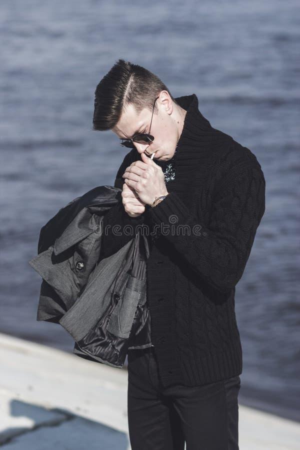 Man i solglasögon som tänder en cigarett royaltyfria bilder