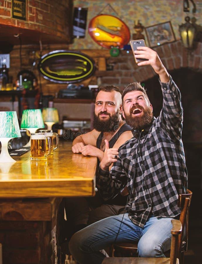 Man i st?ng som dricker ?l Tagandeselfiefoto som minns stor afton i bar Online-kommunikation Sk?ggig hipster f?r man arkivbild