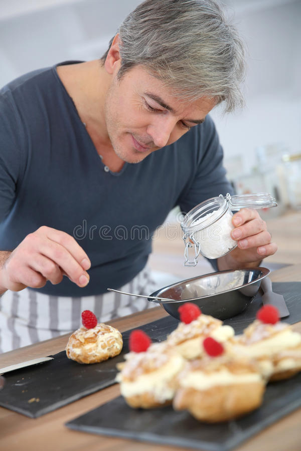Man i stekheta bakelser för kök arkivbild