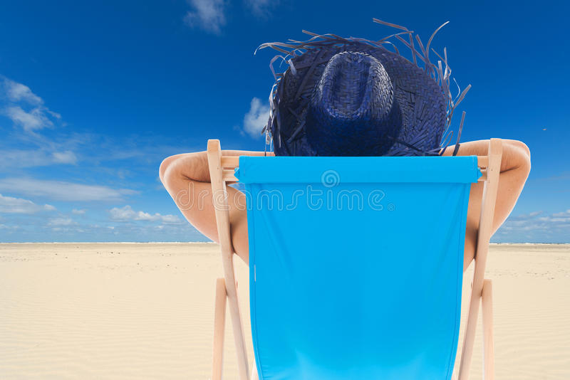 Man i stol på stranden arkivfoton
