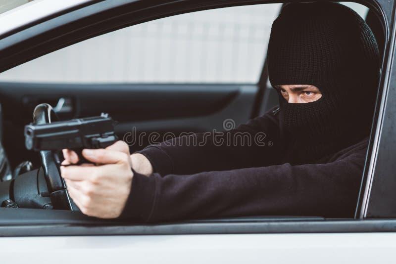 Man i svart balaclava med handeldvapnet som kör en bil arkivfoton