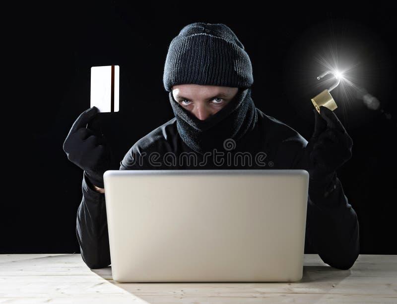 Man i svart hållande kreditkort och lås genom att använda datorbärbara datorn för lösenord för brottslig verksamhetdataintrångban royaltyfri foto