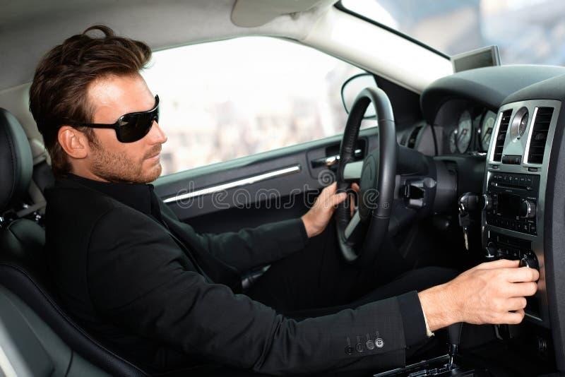 Man i svart i lyxig bil arkivfoton