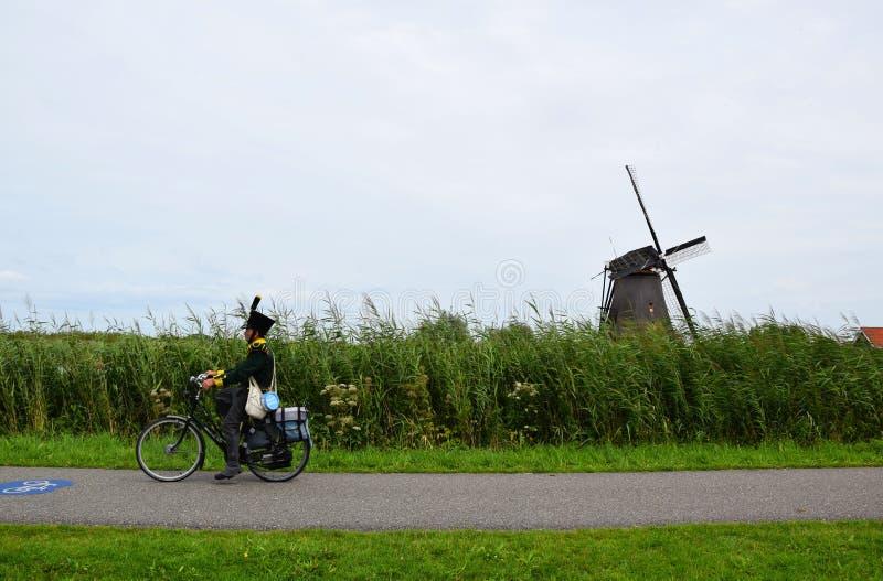 Man i traditionella kläderritter på cykeln längs väderkvarnarna av UNESCOvärldsarvet Kinderdijk, Nederländerna royaltyfri fotografi