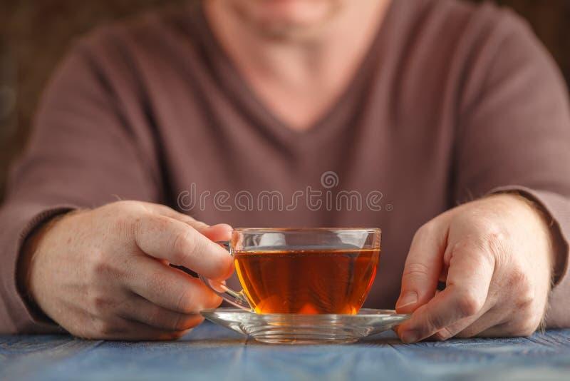Man i varmt te för tröjadrink royaltyfri foto