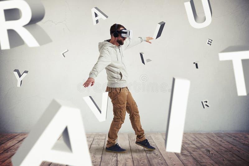Man i virtuell verklighetexponeringsglas som omges, genom att flyga bokstäver arkivfoton