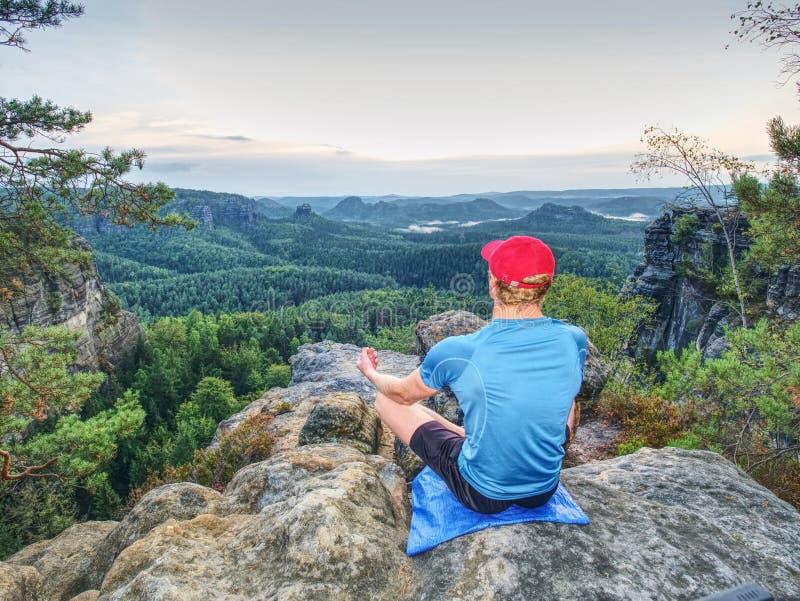 Man i yogaposition i berg ovanför den lösa naturen på solnedgången Begreppet av meditationen, andlighet och anda balanserar royaltyfri fotografi